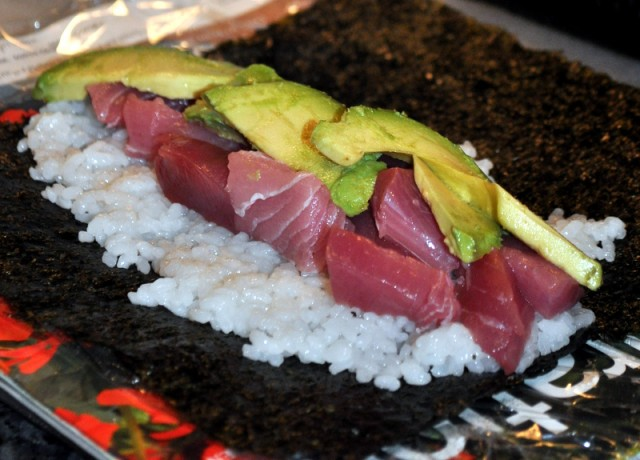 Making a tuna sushi roll.