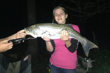 Amber Wechsler of Kunkletown is proudly displaying a 30 inch striped bass that she recently caught at Beltzville Lake during the evening using chicken livers at bait.