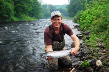 John Kendal, president of the Credit River Anglers Association of Toronto, shows a nice Atlantic salmon before releasing back into the Salmon River near Altmar, NY. The upper fly-fishing section of the Salmon River is open through Nov. 30. (Photo courtesy of John Kendal.)