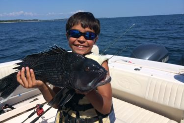 """Mason Baez shows off his 23"""" black sea bass caught on his last day of summer."""