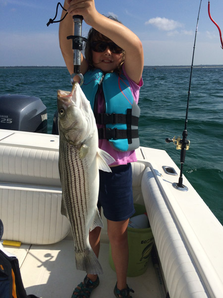 Lily Pawsey, age 9, with a striper caught out of Barnstable Harbor.