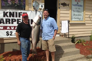 Keith and Wade Colli with the 51-pound striper caught from Boston Harbor on Father's Day.