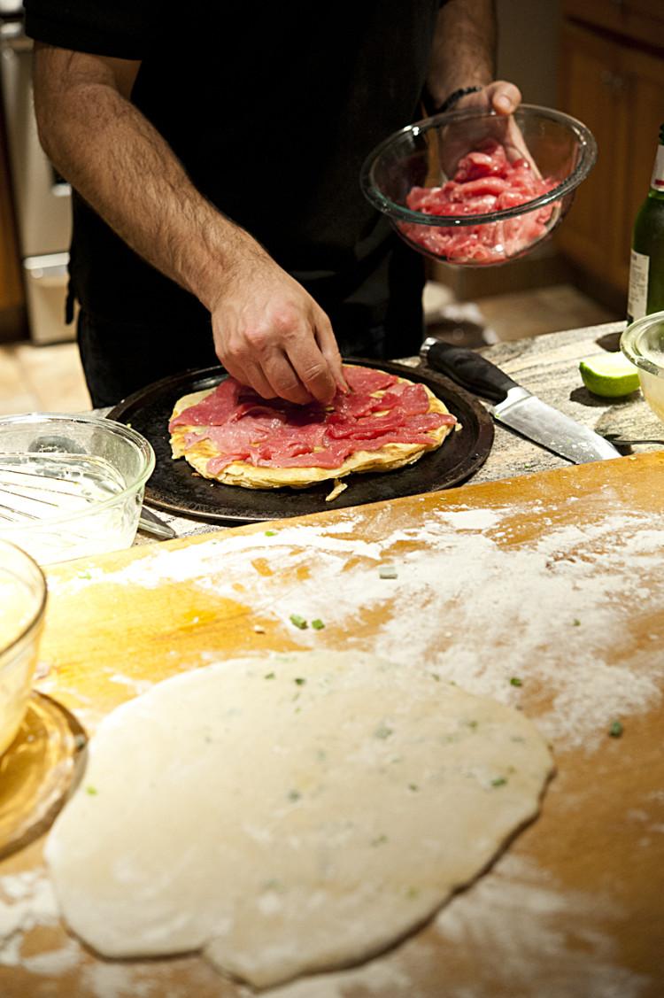 Adding the tuna to the scallion pancake.