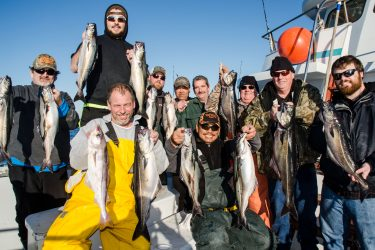 A happy crew of fishermen show off their pollock aboard the Eastman's Fishing Fleet.