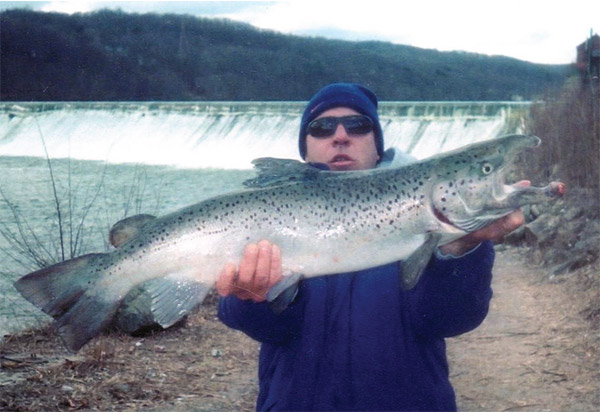 Angler Russ Martin stands in front of the Derby Dam with a large Atlantic salmon