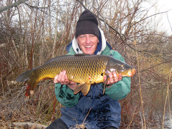 The author holds a common carp of about 14 pounds, taken right after ice out in early March last year. It was caught on sweet corn fished on a hair rig. Carp will begin hitting in shallow ponds as soon as the ice leaves.