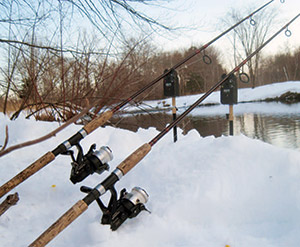 The rods are set on bite alarms and rod holders in a bank of snow along the Blackstone River. Heavy duty freshwater tackle like 7-foot rods, bait-feeder reels and 12-pound-test line work well for wintertime carp fishing.