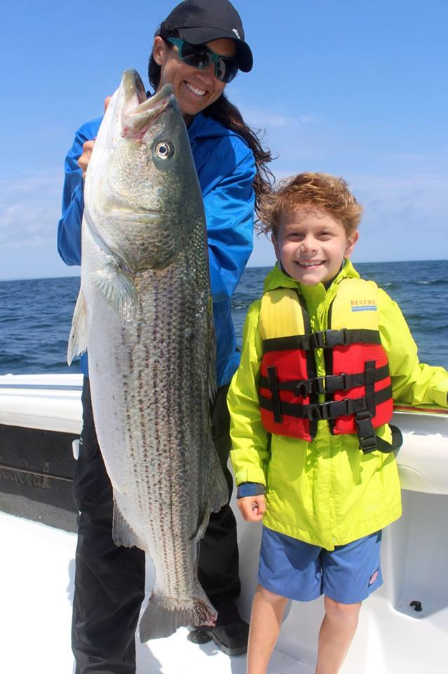 Elena Rice of Reel Deal Fishing Charters holds a big August striper for a happy young angler.