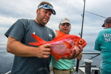 The surprise catch of the trip  made by Dave Arbeitman, right, was this broad alfonsino, a beautifully colored deepwater fish with an enormous eyeball.