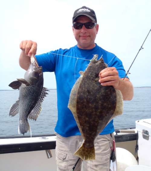 Captain Tom with a fluke on the teaser and a sea bass on the bucktail.