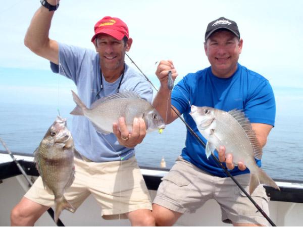 """Rich Lazar with a double, while Captain Tom Mikoleski shows off a big """"pork chop"""" porgy."""