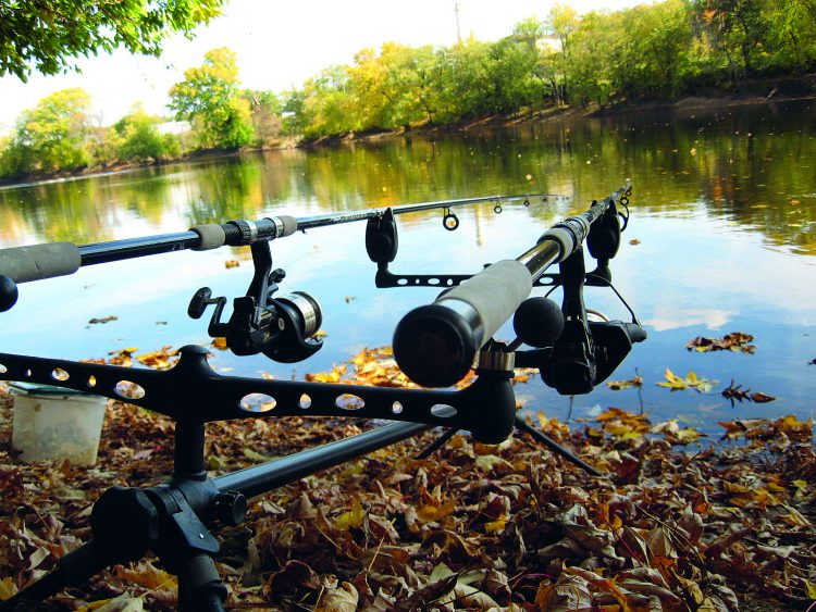 A couple of outfits sit on a rod pod waiting for a hit along the Merrimack River. Note the bait-feeder reels, probably the most important piece of equipment for carp fishing.