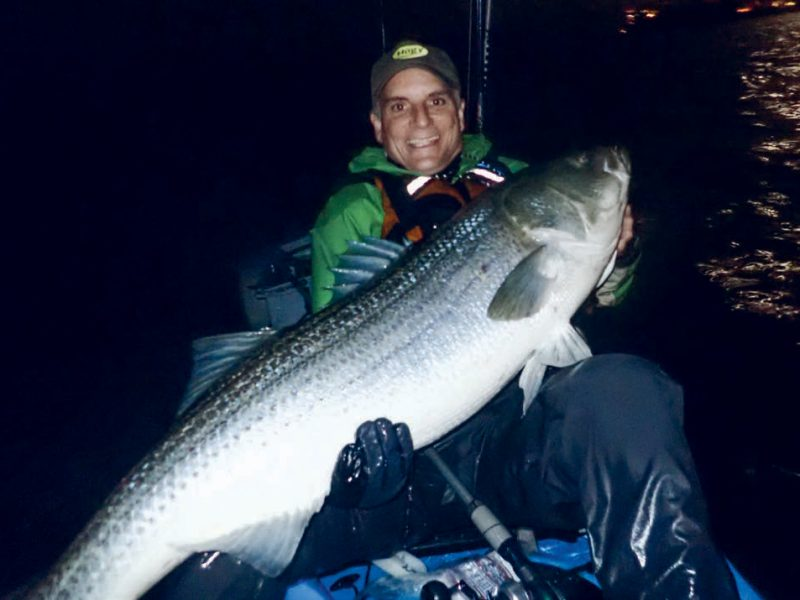 Eric Harrison with a large striper caught in a pedal kayak.