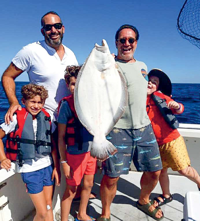 Darren Jacob celebrating with his family after catching this 9.5-pound fluke last August.