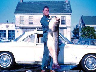 Herbie Dickinson struggles to lift his 64-pound striper with the author's 1964 Corvair Monza in the background.