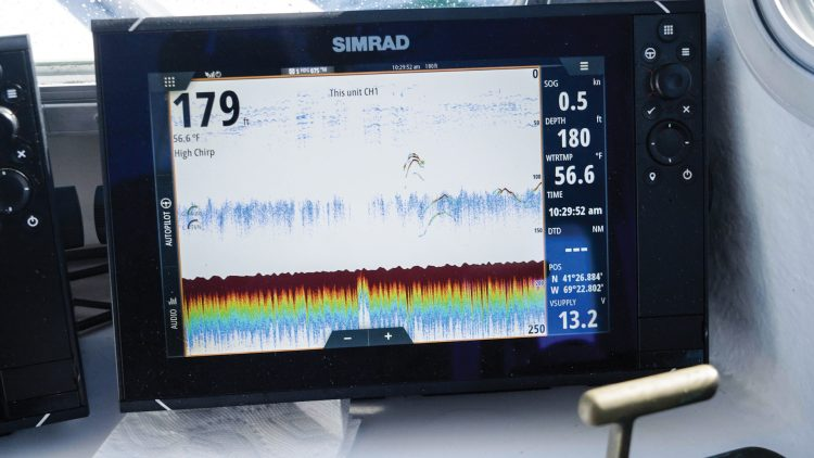 The fish finder sonars shows giant bluefin tuna swimming through schools of baitfish below the surface.