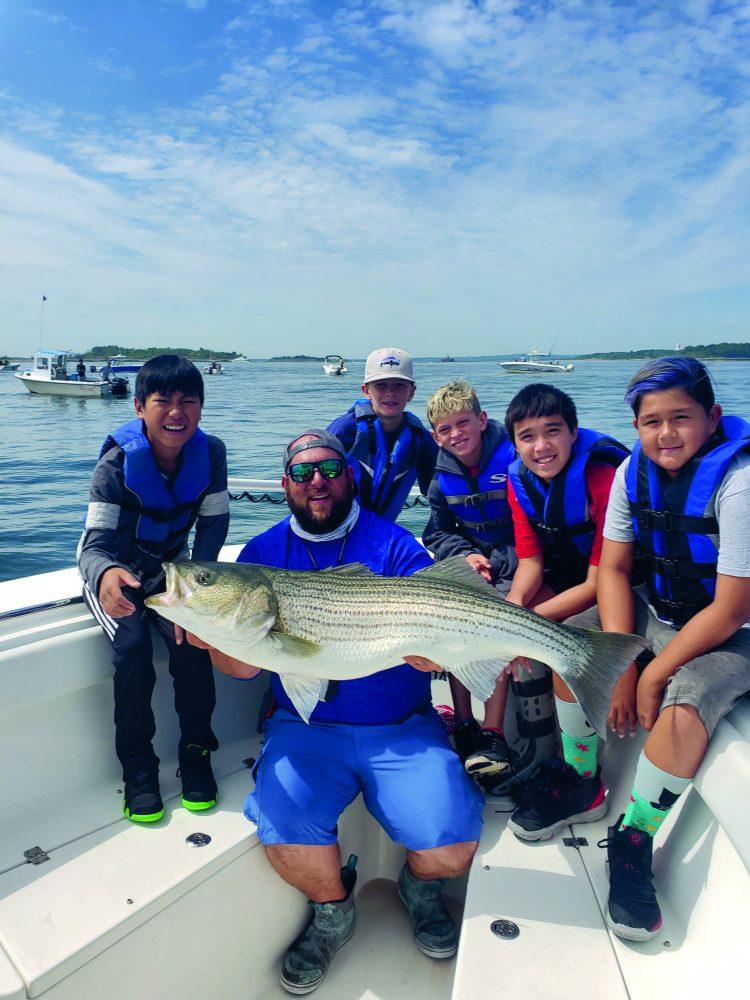 A crew of happy young fishermen with a beautiful striper after learning the ropes of fishing for big bass around schools of bunker from Captain Brian Coombs.