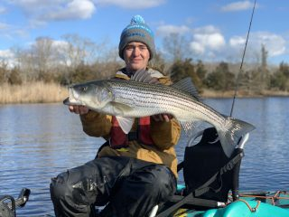 Evan Kamoen holding a holdover striper from a recent kayak fishing trip.