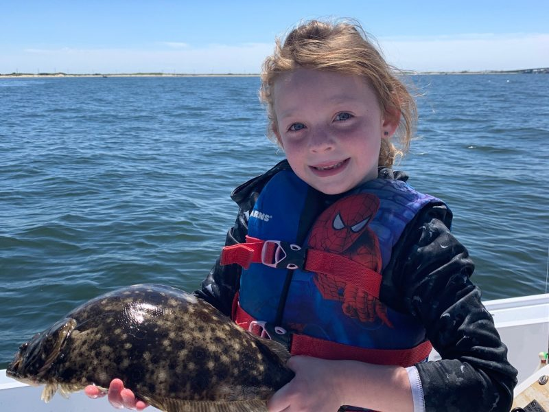 7-year-old Julia Moore holding a fluke that was caught in Sandy Hook Bay, New Jersey.
