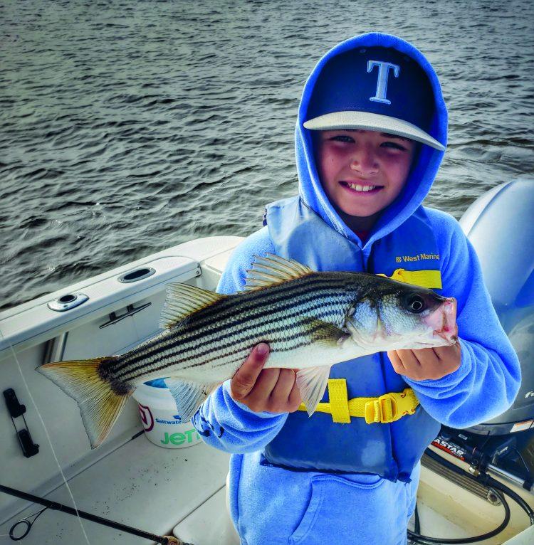 Boy holding striped bass